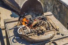Calefacción del metal en la fragua en los carbones Imágenes de archivo libres de regalías