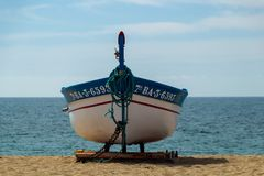 White and blue colored rowboat on the beach royalty free stock image