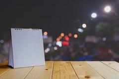 Calendário branco na tabela de madeira no bokeh claro escuro Imagem de Stock