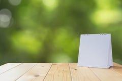 Calendário branco na tabela de madeira no fundo da natureza Foto de Stock