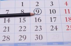 Calendário com um lápis e um círculo pretos Fotos de Stock