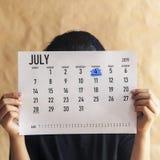 Calendário da terra arrendada da mulher com dia o 4 de julho de 2019 marcado - Dia da Independência dos E.U. foto de stock