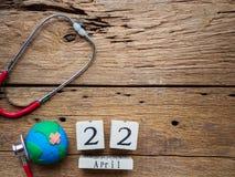 Calendário de bloco de madeira para mundo Dia da Terra o 22 de abril, estetoscópio Fotos de Stock