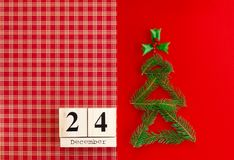 Calendário de madeira com data do 24 de dezembro no fundo vermelho Ano novo e conceito do Natal, decorações do feriado fotografia de stock royalty free