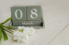 Calendário de madeira com o 8 de março e floowers no fundo branco Imagem de Stock Royalty Free