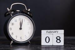 Calendário de madeira da forma do cubo para o 8 de fevereiro com pulso de disparo preto Fotos de Stock Royalty Free