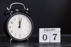 Calendário de madeira da forma do cubo para o 7 de fevereiro com pulso de disparo preto Imagens de Stock
