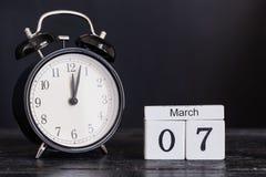 Calendário de madeira da forma do cubo para o 7 de março com pulso de disparo preto Fotografia de Stock Royalty Free