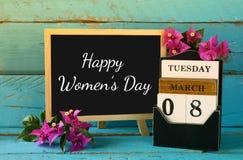 Calendário de madeira do 8 de março, ao lado das flores roxas na tabela rústica azul velha Foco seletivo Vintage filtrado Fotografia de Stock Royalty Free