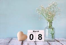 Calendário de madeira do 8 de março, ao lado do coração e das flores brancas na tabela rústica velha Foco seletivo Imagem de Stock Royalty Free