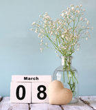 Calendário de madeira do 8 de março, ao lado do coração e das flores brancas na tabela rústica velha Foco seletivo Fotos de Stock Royalty Free