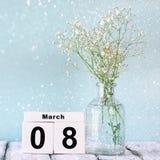 Calendário de madeira do 8 de março, ao lado do coração e das flores brancas na tabela rústica velha Foco seletivo Fotografia de Stock