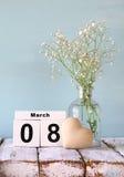Calendário de madeira do 8 de março, ao lado do coração e das flores brancas na tabela rústica velha Foco seletivo Imagens de Stock