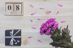 Calendário de madeira do 8 de março, ao lado das flores roxas na tabela de madeira Imagem de Stock Royalty Free