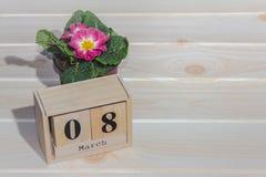 Calendário de madeira do 8 de março, ao lado dos potenciômetros de flor na tabela de madeira Imagem de Stock Royalty Free