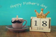 Calendário de madeira do vintage 18o junho ao lado da xícara de café e do bigode Fotos de Stock Royalty Free