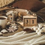 Calendário de madeira do vintage velho ajustado nos 31 de dezembro com o copo com chá ou café, cookies na forma dos flocos de nev imagens de stock