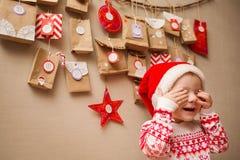 Calendário do advento para crianças criança em um tampão e nos pijamas do Natal felizes e que jogam o auge uma vaia foto de stock royalty free