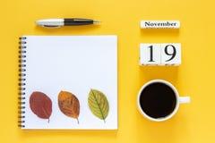 Calendar чашка кофе 19-ое ноября, блокнот с ручкой и желтые лист на желтой предпосылке стоковая фотография rf