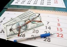 A calendar. Calendar, glasses, pen and dollads Stock Image