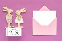 Calendar April 28, pair wooden easter bunnies, pink envelope with blank card on purple paper background. Concept stock photo