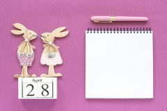 Calendar April 28, pair wooden easter bunnies, white notepad on purple paper background. Concept Christian Easter Mockup stock photos