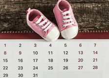 Little baby shoes with calendar. Calendar with baby booties on wooden background Royalty Free Stock Image