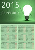 Calendar 2015, be inspired. Text, light bulb character in moment of insight standing on green background Stock Images