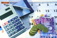 Calendar, checkbook, calculator, money and a ballpen. Photo of a calendar, checkbook, calculator, money and a ballpen Stock Photo