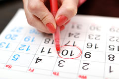 Calendar. Close-up of woman highlighting date on calendar Royalty Free Stock Image