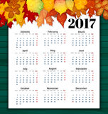 Calendar for 2017 with colorful leaves on wooden background vect. Or Royalty Free Illustration