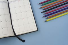 Calendar with colorful pencils on a solid, pastel blue background. Flat lay, space for text.