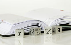 Calendar and a diary. Calendar made ​​of steel cubes and an open diary Stock Image