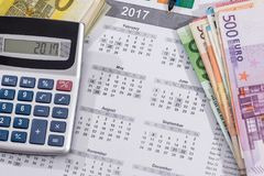 Calendar with euro bills with calculator pen. 2017 calendar with euro bills with calculator pen Royalty Free Stock Photography