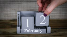 12 calendar February months. 12 setting date on wooden cube calendar for February months stock video