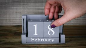 18 calendar February months. 18 setting date on wooden cube calendar for February months stock video