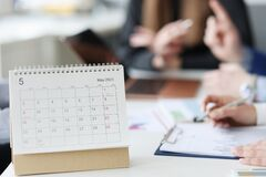 Free Calendar For May Is On Desktop Against Background Of Employees Stock Images - 216715394