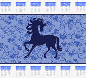 Calendar for 2014 with a horse on a blue backgroun. D with leafy pattern royalty free illustration