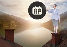 Calendar icon and Businesswoman standing on Roofs with chimney and lake mountain landscape. Digital composite of Calendar icon and Businesswoman standing on Stock Photo