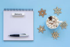 Calendar January and cup of cocoa with marshmallow, empty open notepad royalty free stock image