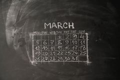 Calendar month March is painted on a chalkboard. The calendar month March is painted on a chalkboard Royalty Free Stock Image