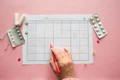 Calendar for the month and the mark of the menstrual cycle. PMS and the critical days concept. Pain pills and personal care products, female hand makes a mark stock photos