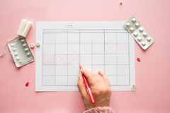 Calendar for the month and the mark of the menstrual cycle. PMS and the critical days concept. Pain pills and personal care products, female hand makes a mark stock image