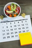 Calendar with new year resolution and diet food. On wooden table stock photo