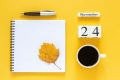 Calendar November 24 cup of coffee, notepad with pen and yellow leaf on yellow background stock photography