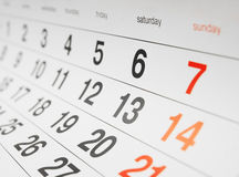 Calendar page. Closeup of a calendar page with black, red and orange date numbers Royalty Free Stock Images
