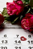 Calendar page with the red hearts and bouquet of red roses on Valentines day. Royalty Free Stock Photo