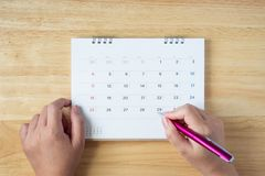 Calendar page on table with female hand holding pen. Top view royalty free stock photos