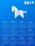 Calendar for 2014 with a paper horse. White origami horse and white calendar grid on a blue background vector illustration