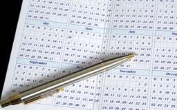 Calendar with Pen. Calendar with a pen over black background Royalty Free Stock Photos